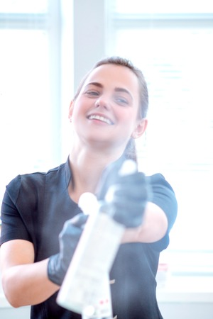 Woman in gloves and with antibacterial spray