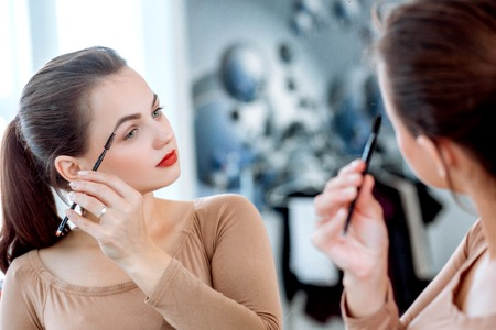 Woman looking in the mirror combing her eyebrows