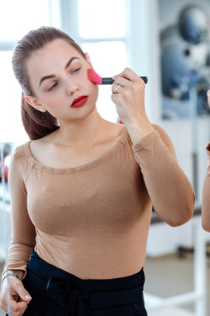 Woman holds cosmetic brush in the face