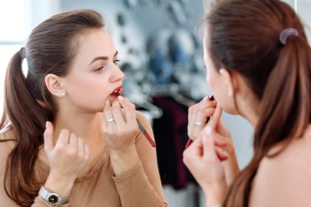 Woman paints her lips with red lipstick Stock fotó - 122535336