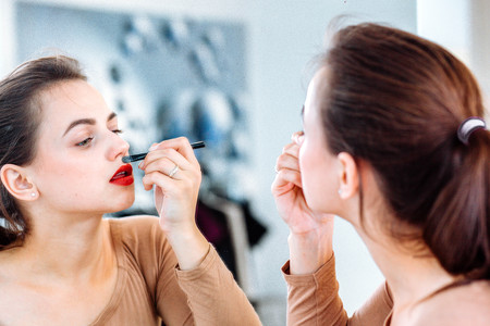 Woman paints her lips with red lipstick