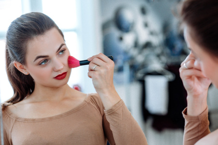 Woman holds cosmetic brush in the face Stock fotó - 122535341