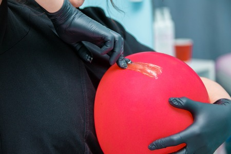 Girl in black gloves shaves a balloon
