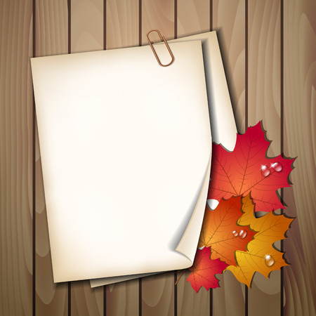 edge design: Paper sheet with autumn leaves on wooden background texture.