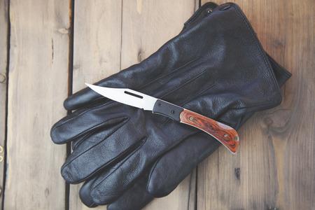 hitman: knife on black gloves on wooden table