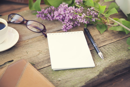 school notebook: cup of coffee, pen, notepad, papers, glasses and flower on wooden table Stock Photo
