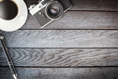 coffee, camera and pen on wooden table