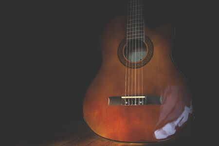 professional flute: Acoustic guitar against on the wooden background.
