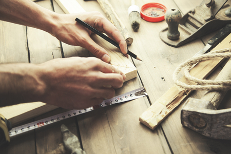 priming brush: Artist canvas on man hand , canvas stretcher and staple gun on table