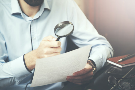 researches: Businessman looking through a magnifying glass to documents