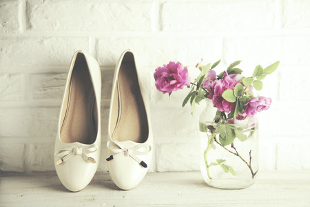 woman shoes and  pink rose on brick wall background