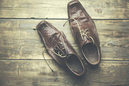 foot gear: male brown shoes over the wooden table