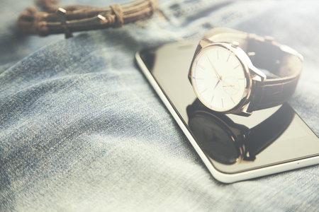 man watch and phone on jeans
