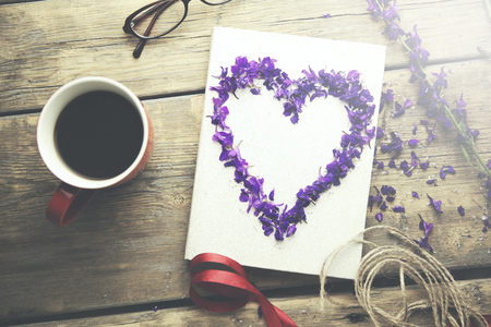 flower petals, heart, headphones, coffee and book on wooden table Reklamní fotografie