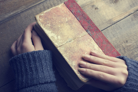 opens: woman opens the book, to read