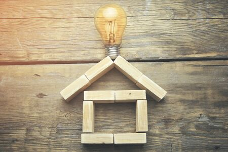 symbolics: light bulb and toy wooden house isolated on wooden background