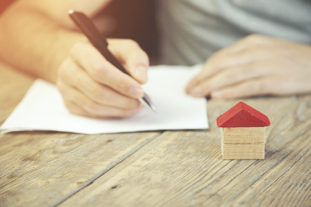 business concepts. Man hand pen and house on wooden table Stock Photo