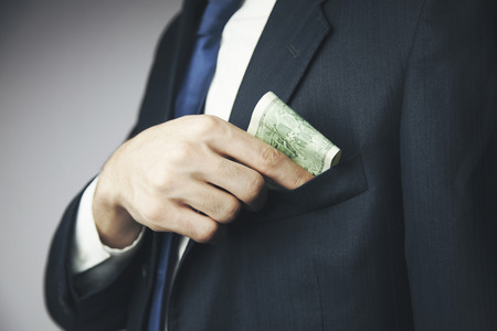hides: Man hides a bribe into a pocket of his jacket Stock Photo