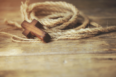 wooden cross and rope on wooden table