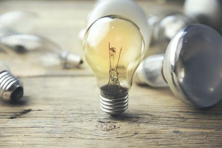 leuchtende Glühbirne Einzigartigkeit Konzept auf Holztisch