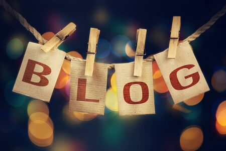 printmaking: The word BLOG spelled out on clothespin clipped cards in front of glowing lights. Stock Photo