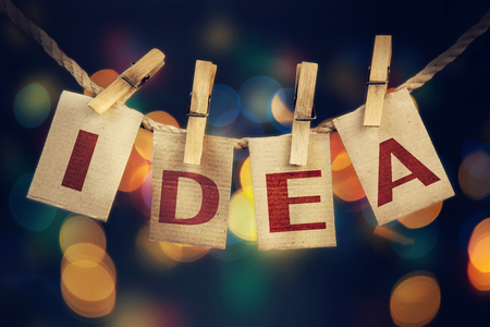 The word IDEA printed on clothespin clipped cards in front of defocused glowing lights.