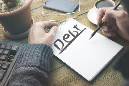 Mann writing debt word on notepad