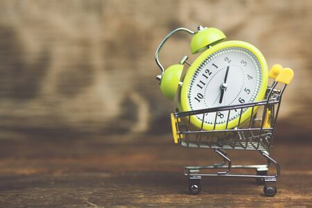 Shopping Cart with Alarm Clock on a wooden background Stock Photo