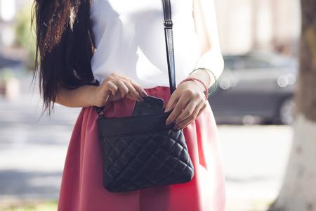 jeune femme élégante de prendre le téléphone portable de sac à main Banque d'images