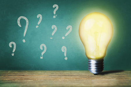 Question text on green board and light bulb on table Stock Photo