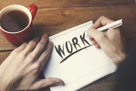 post: Work  text on page,man hand pen and tea  on wooden table Stock Photo