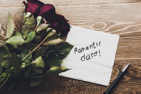 romantyczna data na serwetce i czerwone róże na drewnianym stole Zdjęcie Seryjne