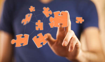Businessman in his office holding puzzle pieces flying over his hand
