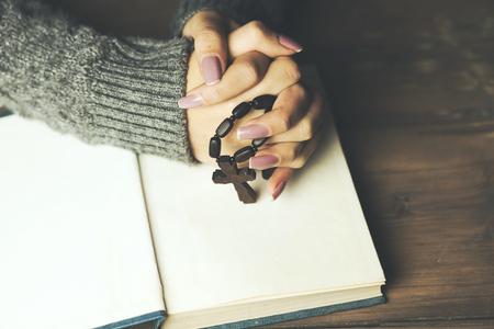 Vrouw bidden met bijbel en kruist op tafel