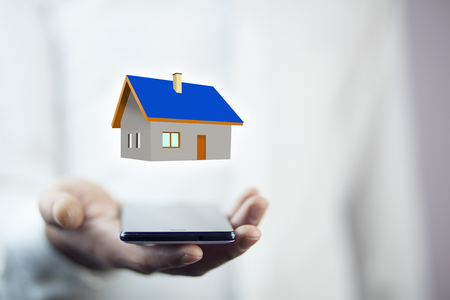 Man hand phone with  house model Stock Photo