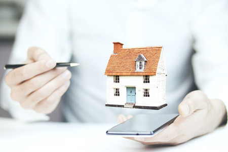 Man hand phone with house model on white background