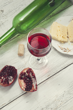 pomegranate, wine and  cheese on the table