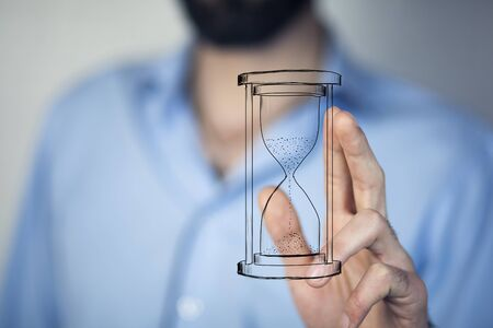 Man's hand holding hourglass sand  Stockfoto