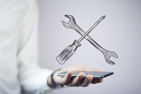 man hand  phone and  tools in screen Stock Photo
