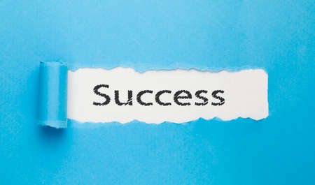 success text written on paper on blue background