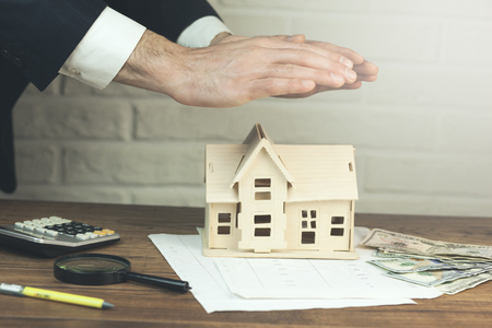 man hand house model  with calculator and money on table Stock Photo