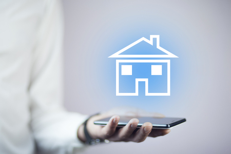 man hand phone with house in screen