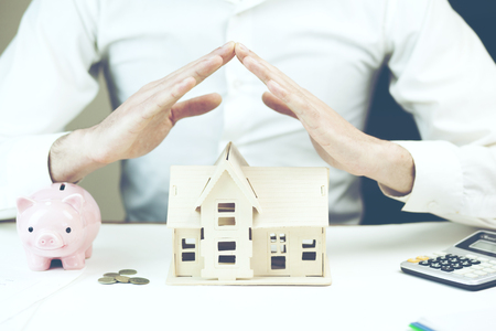 Man protecting his house with calulator and piggy bank on table Stock Photo