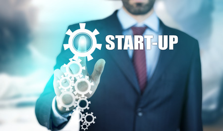 business man hand start-up text in screen Stock Photo