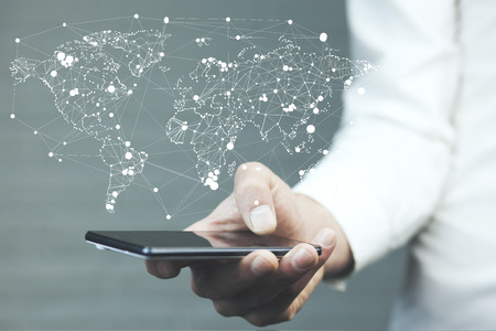 businessman hand phone with world map on screen Фото со стока