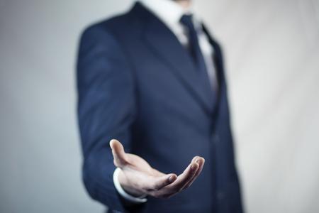 mannetje staat en toont uitgestrekte hand met open palm Stockfoto