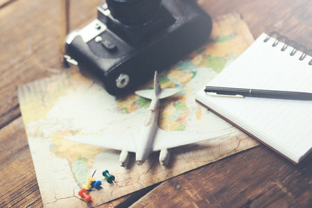 travel accessories: camera, map,airplane with notepad on wood background