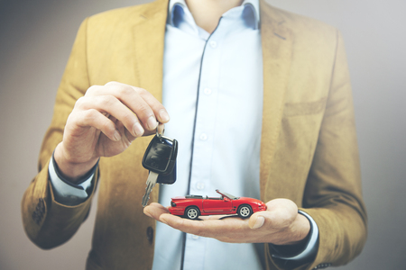 young business man hand holding red car and key