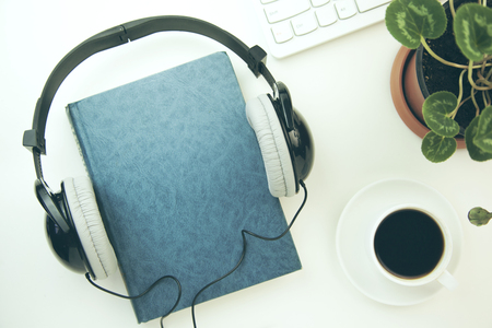 Headphones and  book with keyboard on the  white table Stockfoto