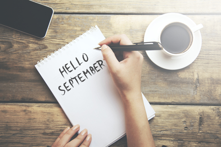 woman written hello september text on notepad with phone and coffee on table